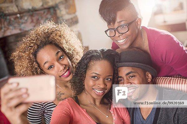 Vier erwachsene Freunde posieren für Smartphone Selfie auf dem Sofa
