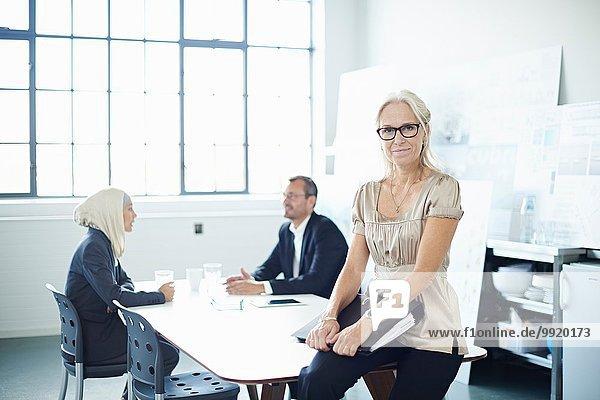 Porträt einer reifen Geschäftsfrau  die auf dem Schreibtisch sitzt.