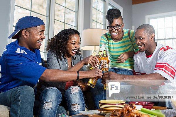 Vier erwachsene Freunde stoßen mit Flaschenbier auf dem Wohnzimmersofa an.