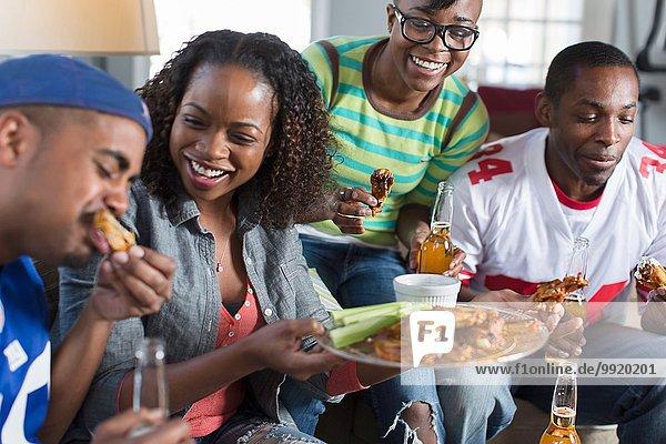 Gruppe erwachsener Freunde beim Essen auf dem Wohnzimmersofa