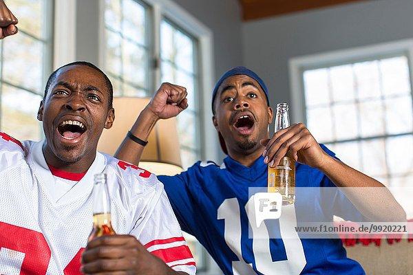 Zwei männliche Freunde feiern  während sie vom Sofa aus fernsehen.