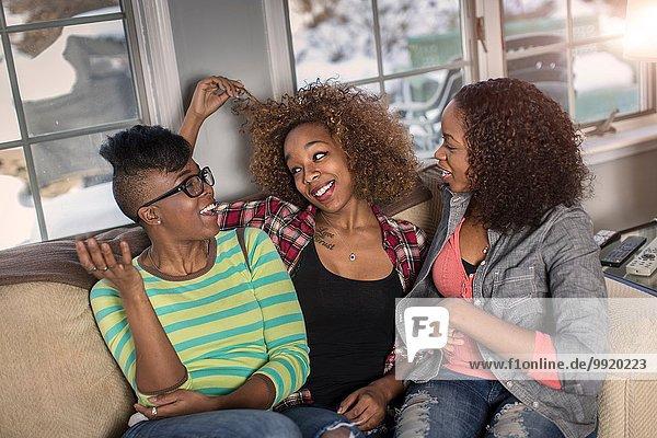 Drei Freundinnen beim Plaudern auf dem Wohnzimmersofa