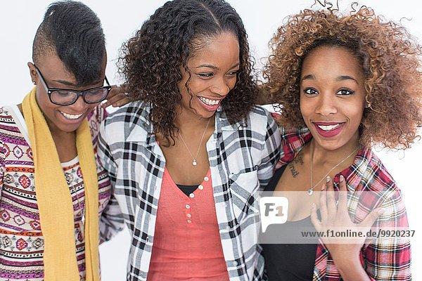 Studio-Porträt von drei lächelnden jungen Freundinnen