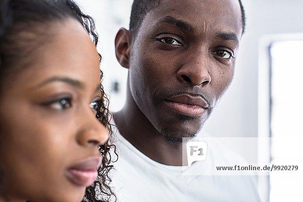 Studio-Porträt eines selbstbewussten  erwachsenen Mannes neben der Freundin