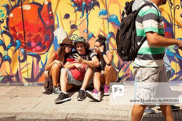 Drei junge erwachsene Hipster sitzen auf dem Bürgersteig und lesen Smartphone-Texte  Rio De Janeiro  Brasilien