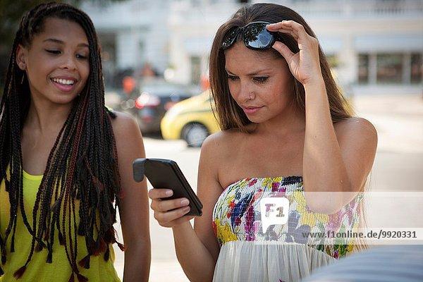 Zwei junge Freundinnen beim Lesen von Texten auf dem Smartphone  Copacabana  Rio De Janeiro  Brasilien