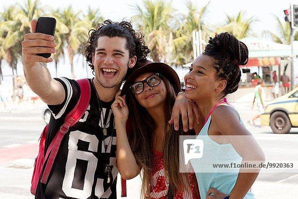 Drei junge erwachsene Freunde posieren für Smartphone Selfie  Copacabana  Rio De Janeiro  Brasilien
