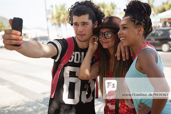 Drei junge erwachsene Freunde mit Smartphone Selfie  Copacabana  Rio De Janeiro  Brasilien