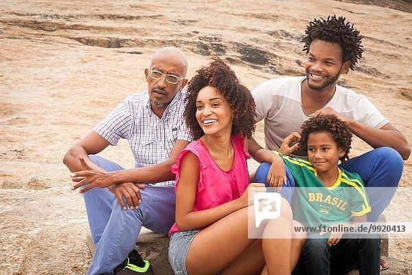 Großvater und Familie sitzen am Felsen  Ipanema Beach  Rio De Janeiro  Brasilien