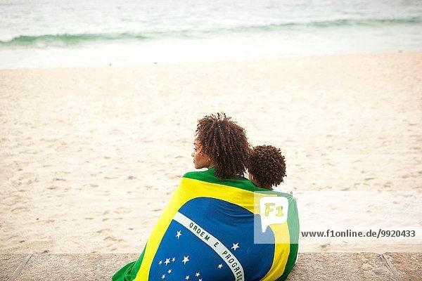 Rückansicht von Mutter und Sohn in brasilianischer Flagge mit Blick vom Strand von Ipanema  Rio De Janeiro  Brasilien.