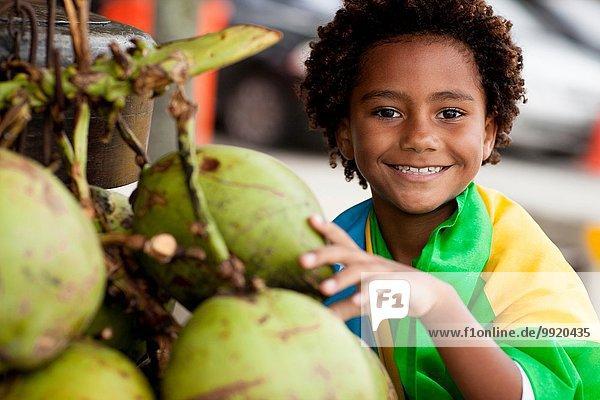 Porträt eines Jungen in brasilianischer Flagge  der am Strand von Ipanema  Rio De Janeiro  Brasilien  Kokosnuss auswählt.