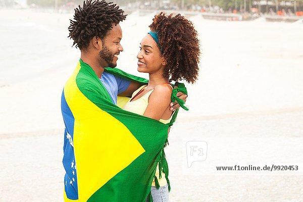 Lächelndes Paar in brasilianischer Flagge am Strand von Ipanema  Rio De Janeiro  Brasilien