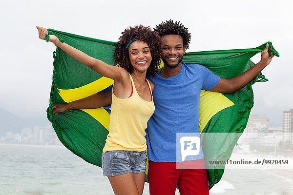 Porträt eines Paares mit brasilianischer Flagge am Strand von Ipanema  Rio De Janeiro  Brasilien
