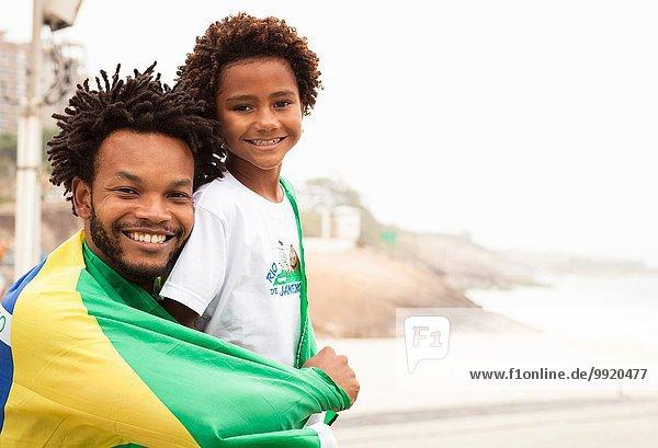 Porträt von Vater und Sohn in brasilianischer Flagge am Strand von Ipanema  Rio De Janeiro  Brasilien