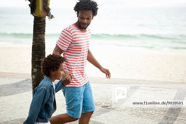 Vater und Sohn laufen Hand in Hand am Strand von Ipanema  Rio De Janeiro  Brasilien