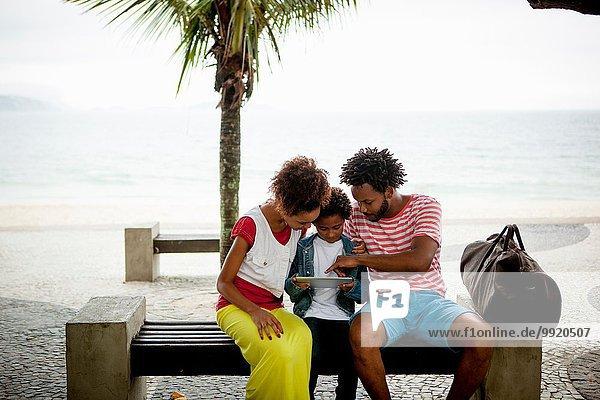 Paar und Sohn sitzen auf einer Parkbank mit digitalem Tablett  Ipanema Beach  Rio De Janeiro  Brasilien