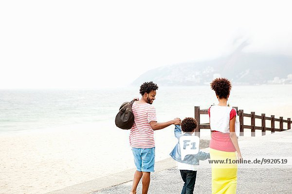 Rückansicht von Paar und Sohn  die Hand in Hand schlendern  Ipanema Strand  Rio De Janeiro  Brasilien