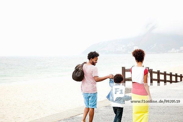 Rear view of couple and son strolling hand in hand  Ipanema beach  Rio De Janeiro  Brazil