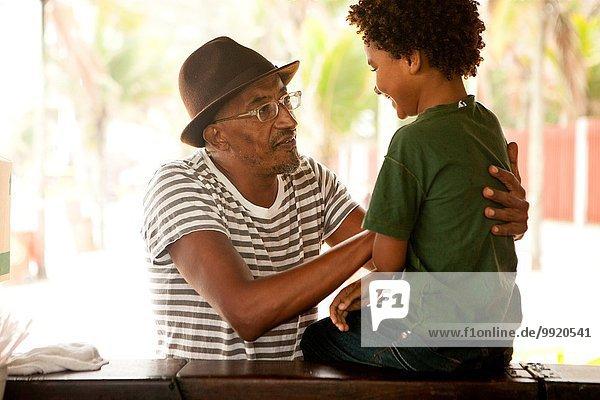Erwachsener Mann im Gespräch mit Enkel auf der Bar  Ipanema Strand  Rio De Janeiro  Brasilien