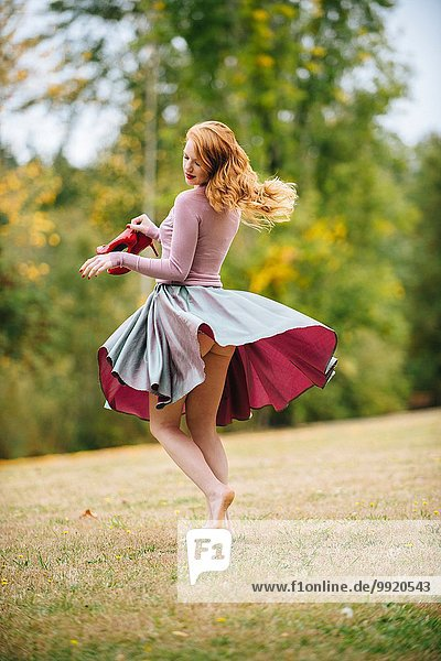 Young woman dancing in park revealing bare buttocks
