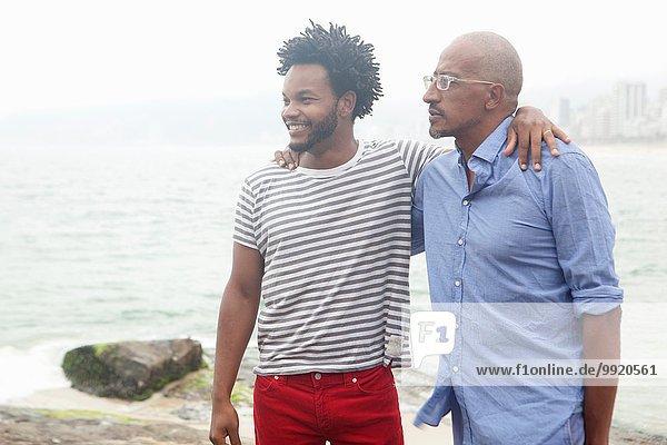 Erwachsener Mann und Sohn mit Armen umeinander  Strand von Ipanema  Rio De Janeiro  Brasilien