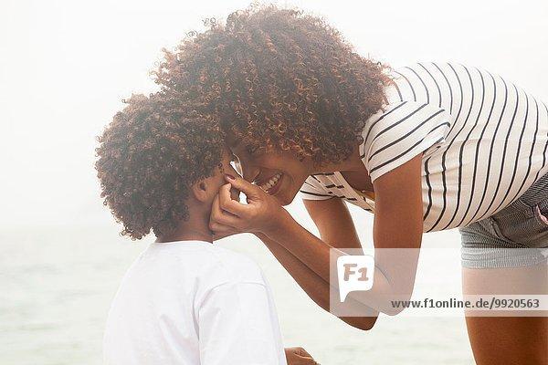 Porträt einer jungen Frau  die die Wangen ihrer Söhne berührt  am Strand von Ipanema  Rio De Janeiro  Brasilien