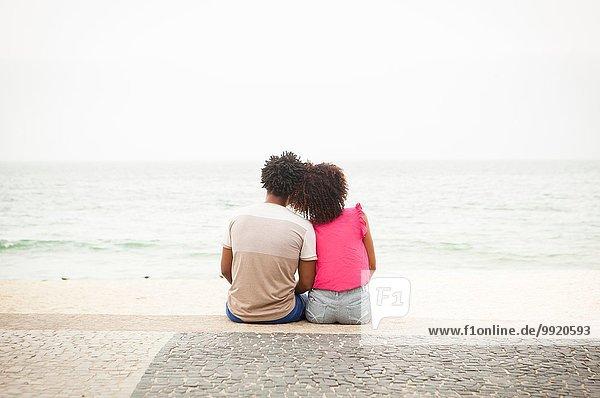 Rückansicht des romantischen Paares mit Blick auf den Strand von Ipanema  Rio De Janeiro  Brasilien