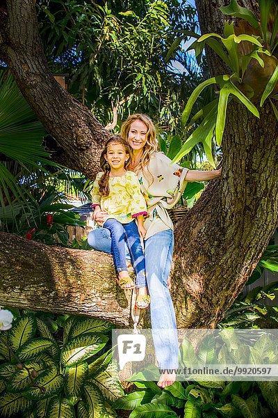 Mutter und Tochter sitzen auf einem Gartenbaumzweig