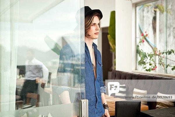 Stilvoller junger Mann mit Blick aus der Hotellobby