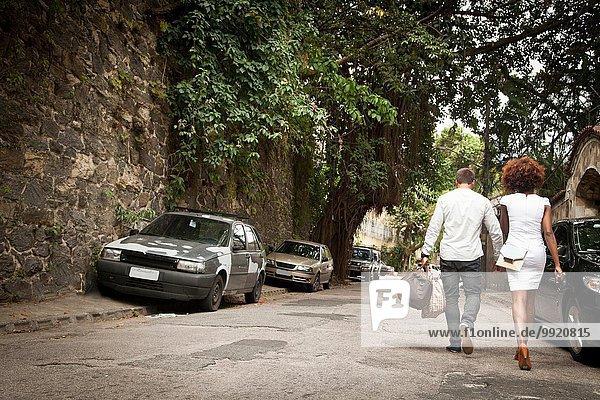 Ein Paar  das auf der Straße geht und Händchen hält.