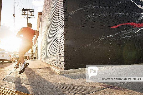 Rückansicht des männlichen Läufers auf dem Bürgersteig