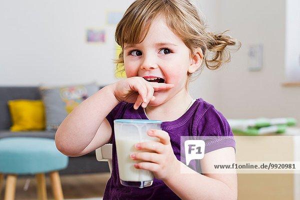 Mädchen mit einem Glas Milch zu Hause