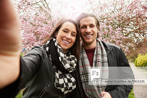 Young couple posing for selfie with blossom in park