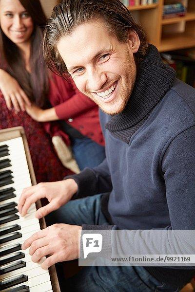 Porträt eines jungen Mannes  der für eine Freundin Klavier spielt