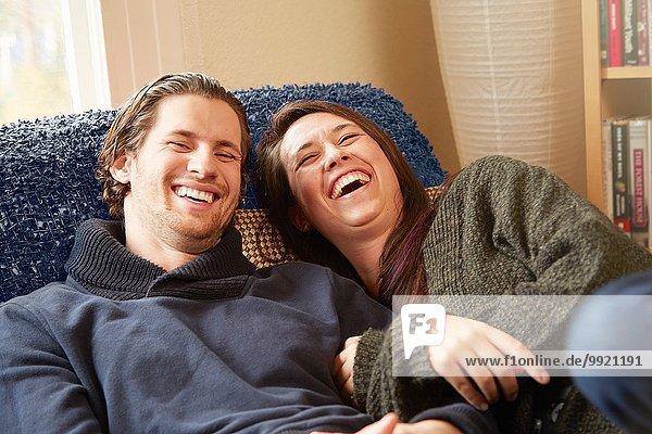 Junges Paar lacht auf dem Wohnzimmersofa