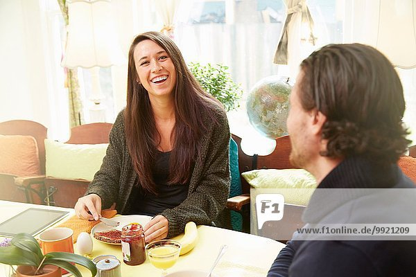 Junges Paar lacht am Frühstückstisch