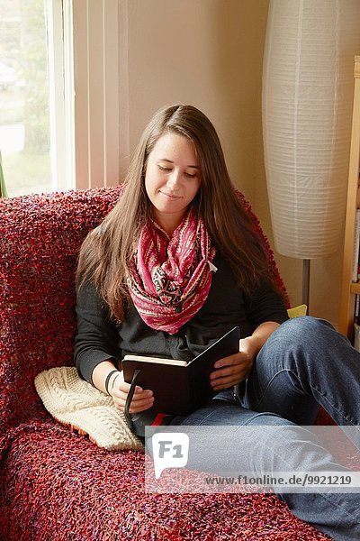 Young woman reclining on sofa reading a book