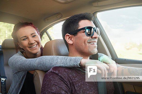 Junge Frau mit Armen um den Freund beim Autofahren