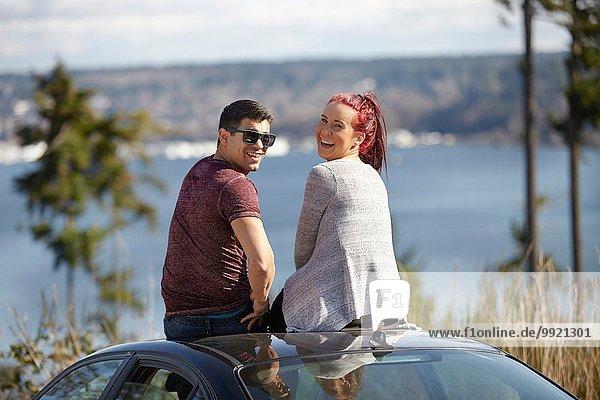 Porträt eines jungen Paares  das auf dem Autodach am Seeufer sitzt und zurückblickt.