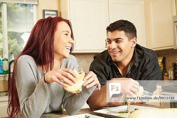 Junges Paar isst Sandwiches an der Küchentheke
