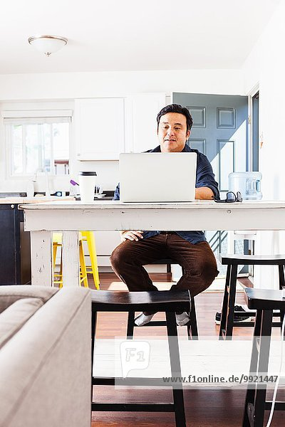 Mature businessman typing on laptop at kitchen table