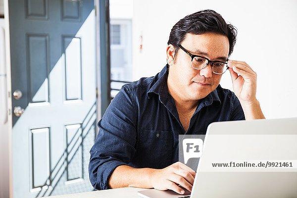 Reife Geschäftsleute konzentrieren sich auf Laptop in der Küche
