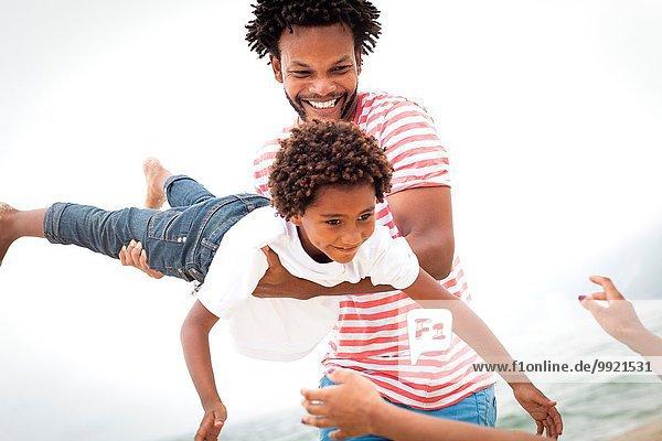 Vater und Sohn spielen am Strand