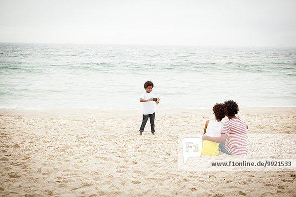 Paar und Sohn fotografieren am Strand