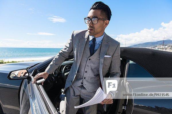 Junger Geschäftsmann steigt mit Papierkram und Smartphone auf dem Küstenparkplatz aus.