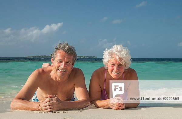 Senior couple lying on beach  Maldives