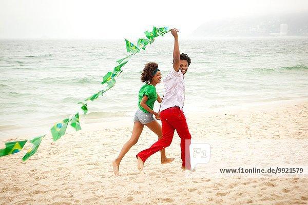 Pärchenspiel mit Fahnenkette am Strand  Rio de Janeiro  Brasilien