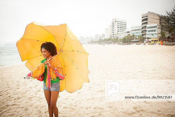 Junge Frau mit Regenschirm am Strand  Rio de Janeiro  Brasilien