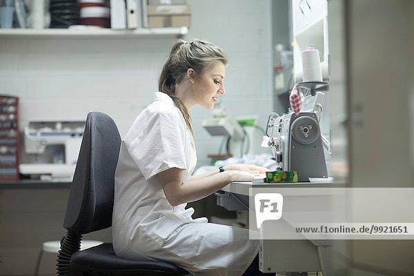Frau arbeitet an der Nähmaschine in der Wäscherei
