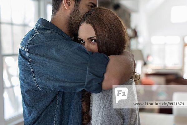 Junger Mann umarmt Frau